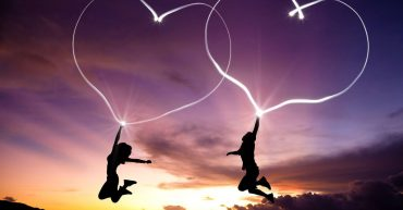 two people jumping with hearts